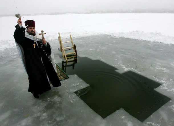 An Orthodox priest blesses the waters of lake Chizhovskoye in celebration of the Epiphany holiday in Minsk on January 19, 2009. For Christians, the Epiphany celebrates the baptism of Christ by John the Baptist in the river Jordan.      AFP PHOTO / VIKTOR DRACHEV (Photo credit should read VIKTOR DRACHEV/AFP/Getty Images)